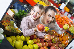 Mother and  cute little daughter choosing seasonal fruits Royalty Free Stock Photography