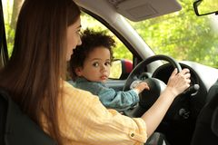 Mother with cute little daughter driving car. Child in danger. Mother with cute little daughter driving car together. Child in danger royalty free stock images