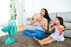Mother with cute little daughter feeling very hot. Pretty mother with cute little daughter feeling very hot at summer day and eating watermelon blowing electric Stock Photos