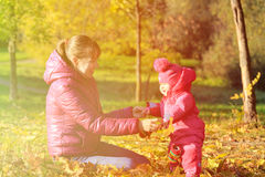 Mother and cute little daughter play in autumn Royalty Free Stock Images