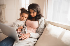 Mother and cute little daughter sitting together on couch and using laptop Royalty Free Stock Images