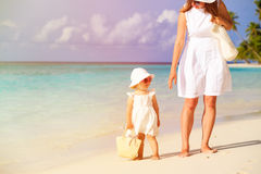 Mother and cute little daughter walking on beach Stock Photos