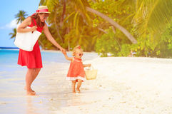 Mother and cute little daughter walking on beach Stock Images