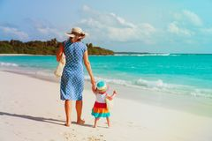 Mother and cute little daughter walking on beach. Mother and cute little daughter walking on tropical beach Royalty Free Stock Photos