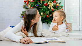 Mother and cute little dautgher lying on the floor and reading book at xmas eve. Happy family mother and cute little daughter lying on the floor and reading Royalty Free Stock Image