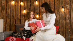 Mother and a cute little girl shaking Xmas presents and trying to guess what`s inside. Professional shot on Lumix GH4 in 4K resolution. You can use it e.g. in Stock Images