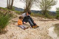 Mother and cute little girl sitting near Bohinj lake during spring time in Slovenia Royalty Free Stock Image