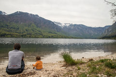 Mother and cute little girl sitting near Bohinj lake during spring time in Slovenia Stock Photo