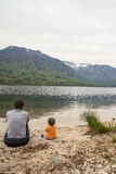 Mother and cute little girl sitting near Bohinj lake during spring time in Slovenia Stock Photography