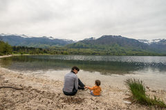 Mother and cute little girl sitting near Bohinj lake during spring time in Slovenia Stock Image