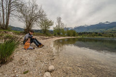 Mother and cute little girl sitting near Bohinj lake during spring time in Slovenia Royalty Free Stock Photography