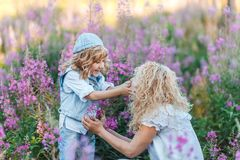 Mother and a cute little son hugging and having fun in the fild with flowers in summer. Family and happiness consept stock images