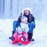Mother and cute little toddler daughter having fun on a sledge i. Young happy mother and cute little toddler daughter having fun on a sledge with riding in a Stock Photos