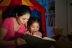 Mother and cute youth kid reading story toy book. Beauty leisurely mother and cute youth kid reading story toy book looking terrible things feeling afraid Stock Photos