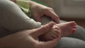A Mother cuts fingernails of a Baby. A Mother cuts fingernails of her Baby stock video footage