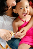 Mother cutting fingernail of a child Royalty Free Stock Photography