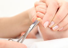 Mother cutting theToenails of a Baby Stock Images
