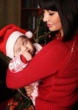 Mother with dark hair with cute little baby  beside Christmas tree Stock Images