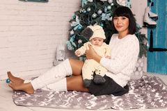 Mother with dark hair with cute little baby sitting  beside Christmas tree Royalty Free Stock Images