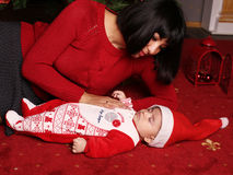 Mother with dark hair with cute little sleeping baby  beside Christmas tree Stock Image