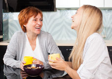 Mother and daudhter talking on the kitchen Royalty Free Stock Images
