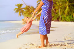 Mother and daugher playing on beach Stock Images