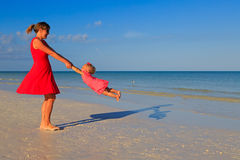 Mother and daugher playing on summer beach Royalty Free Stock Image