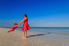 Mother and daugher playing on summer beach Stock Images