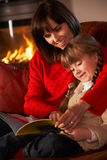 Mother And Daughte Reading A Book. Mother And Daughter Sitting On Sofa And Reading Book By Cosy Log Fire Royalty Free Stock Images