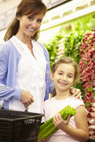 Mother And Daughteer Shopping For Produce In Supermarket Stock Photo
