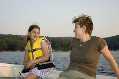 Mother daughter 1. Mother and young daughter sitting on a boat looking at each other Stock Photos