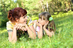 Mother with  daughter. Mother together with the daughter lay on a lawn, smile, look in the face to each other Stock Photography
