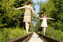 Mother with  daughter. Mother with the daughter go on rails, a back to a camera, in a wood, in the summer Royalty Free Stock Images