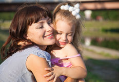 Mother and the daughter. Mother is embracing daughter in a park Royalty Free Stock Photography