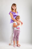 Mother and daughter. Mother and her daughter on gray background Royalty Free Stock Photos