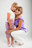 Mother and daughter. Mother and her daughter on gray background Royalty Free Stock Photo