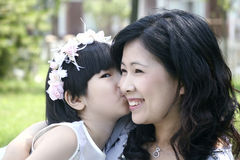 Mother and daughter. Adorable little asian girl is whispering to her mother Royalty Free Stock Photography