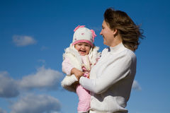 Mother with daughter. Happy mother with the beautiful little girl against the blue sky Royalty Free Stock Photos