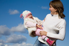 Mother with daughter. Happy mother with the beautiful little girl against the blue sky Stock Photos