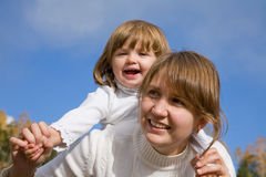 Mother with daughter. Happy mother with the beautiful little girl against the blue sky Stock Images