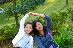 Mother and daughter. In the autumn, younger mother bring her daughter visited the beautiful garden,with the sweet smile, we can felt a warming love of mother Stock Image