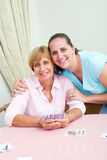 Mother and daughter. Happy senior mother and daughter playing cards together at home Royalty Free Stock Image
