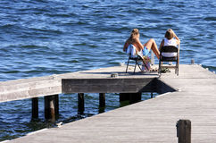 Mother&Daughter. Mother and daughter enjoying the summer sun on a dock in Lake Washington, Seattle, Washington royalty free stock images