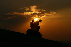Mother and Daughter. Sitting on a rock, against a sunset. This is taken on top of Stone Mountain in Atlanta Stock Photo