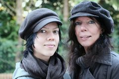 Mother and daughter. Outside together, both wearing hats stock photography