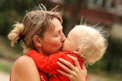 Mother and daughter. Mother kisses daughter on street Stock Images