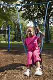 Mother and daughter. Playing at a park (Rope swing Stock Photography