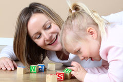 Mother and daughter. Playing with alphabet building blocks Royalty Free Stock Photos