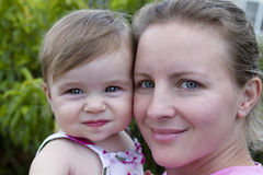 Mother and Daughter. Headshot. Mother looking at camera with a secure, trusting feelings. Smilar impression on 11 months baby Royalty Free Stock Photo