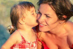 Mother and daughter. Little daughter kissing her mother Stock Photos